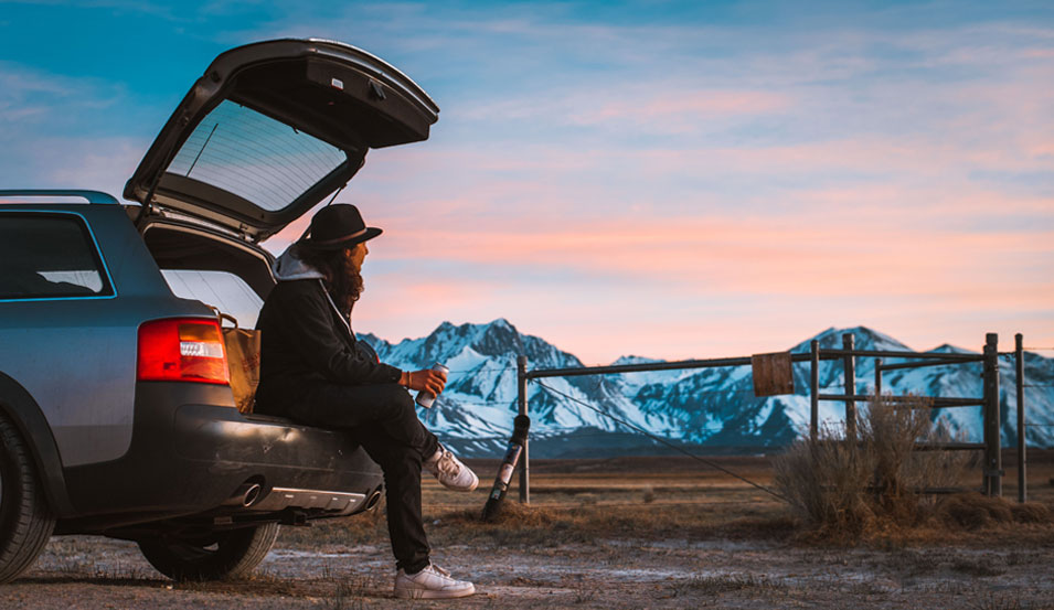man looking at the mountain with his car